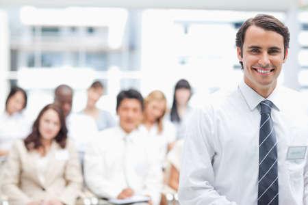 looking ahead: Smiling businessman looking ahead as his colleagues sit behind him LANG_EVOIMAGES