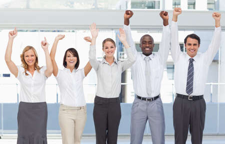 arms above head: Business team smiling while holding their arms above their head LANG_EVOIMAGES