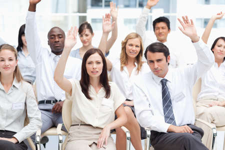 arms above head: Serious colleagues sit together as they raise their arms above their head