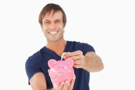 one mid adult male: Piggy bank held by a man and receiving notes against a white background LANG_EVOIMAGES