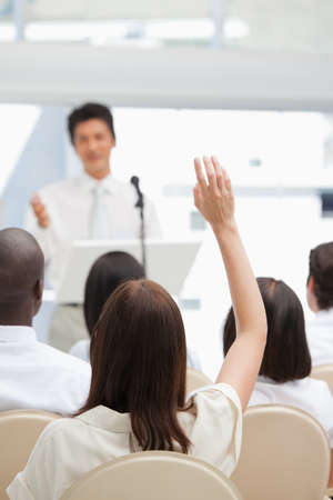raises: Woman sitting in an audience raises her hand as she is being watched by a businessman LANG_EVOIMAGES