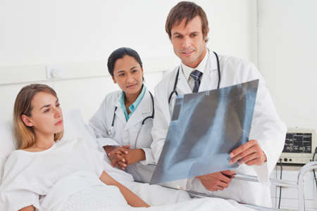 chest xray: Two doctors and a patient looking at a chest x-ray while staying in a hospital room