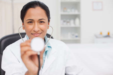 practitioner: Relaxed practitioner holding her stethoscope while sitting in her office