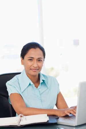 black professional: Calm young secretary working with her laptop while sitting at a desk LANG_EVOIMAGES