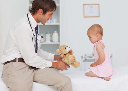 practitioner: Smiling practitioner offering a teddy bear to a little baby after a consultation