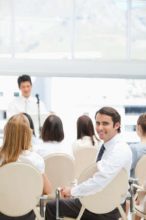 looking behind: Happy businessman looking behind him as he sits with his colleagues during a presentation