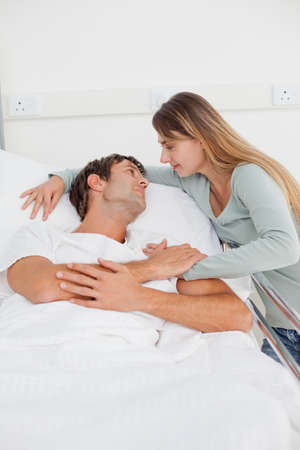 hugged: Relaxed patient lying in a hospital bed while being hugged by his cute wife