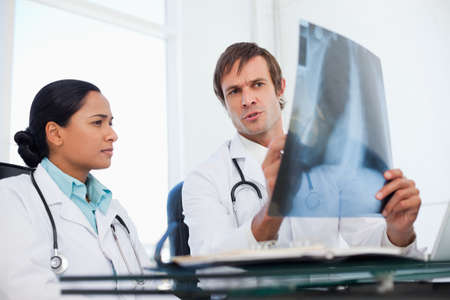 chest xray: Serious surgeons sitting at a desk side by side while talking about a chest x-ray
