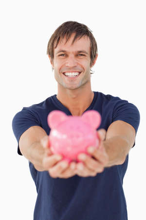 one mid adult man: Smiling man holding a pink piggy bank against a white background