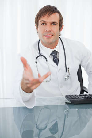 explanations: Doctor raising an eyebrow while sitting at his desk and giving explanations