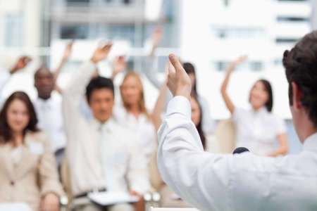 brown haired: Brown haired businessman gesturing towards his colleagues as they have their arms raised