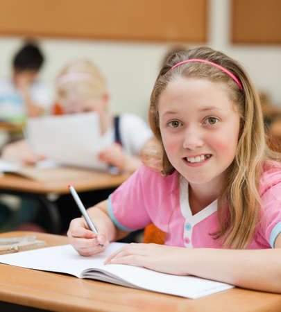 schoolchild: Smiling young female schoolchild sitting at her desk