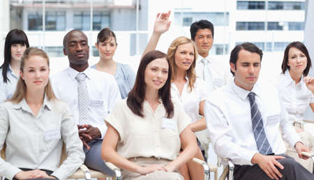 blonde haired: Blonde haired woman raising her arm as she sits in a group of her colleagues LANG_EVOIMAGES