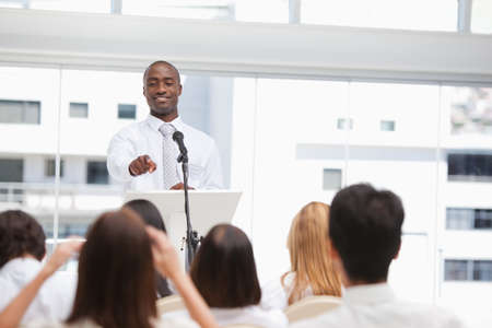 they are watching: Businessman pointing towards a member of the audience as they are watching him