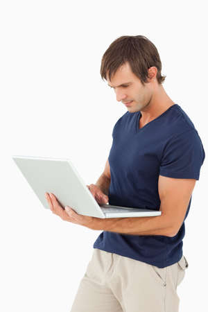 one mid adult male: Serious man holding a laptop against a white background