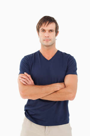 one mid adult male: Man crossing his arms while looking at the camera against a white background
