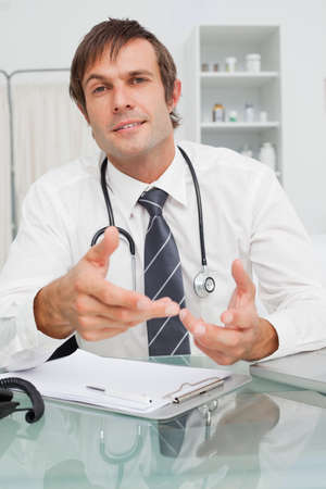 explanations: Relaxed doctor looking straight at the camera while giving some explanations LANG_EVOIMAGES