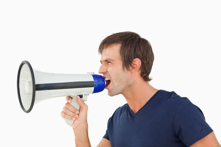 one mid adult male: Furious man shouting through a megaphone against a white background