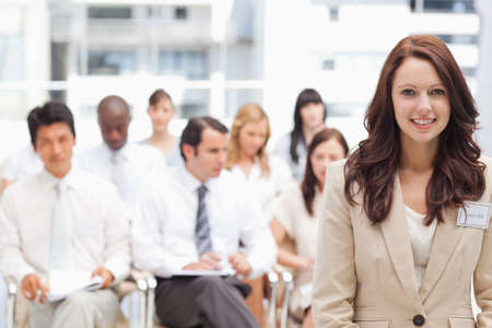 looking ahead: Smiling businesswoman looking ahead while standing in front of her colleagues