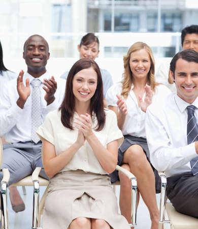 applaud: A group of smiling colleagues look ahead and applaud happily as they sit next to each other LANG_EVOIMAGES
