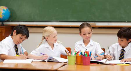 beautiful boys: Little schoolchildren in school uniforms painting at desk