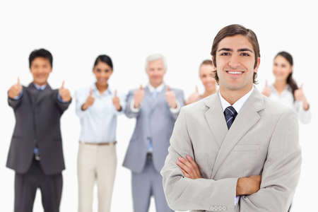 thumbsup: Close-up of a multicultural business team with their thumbs-up focus on a smiling man with his arms folded in foreground