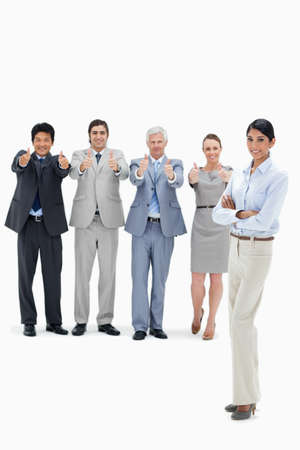 thumbsup: Multicultural business team with their thumbs-up with a smiling woman in foreground against white background LANG_EVOIMAGES