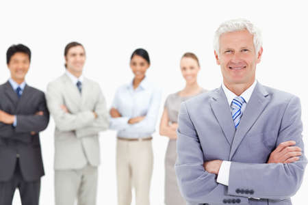 arms folded: Close-up of a smiling multicultural business team with their arms folded focus on a white hair man in foreground LANG_EVOIMAGES