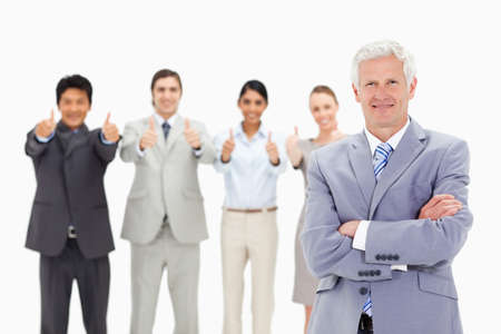 thumbsup: Close-up of a multicultural business team with their thumbs-up with a mature man crossing his arms in foreground LANG_EVOIMAGES