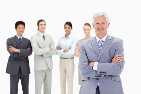 arms folded: Close-up of a smiling multicultural business team with their arms folded focus on a mature man in foreground