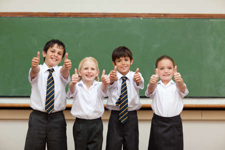 four classes: Smiling little children in school uniforms giving thumbs up