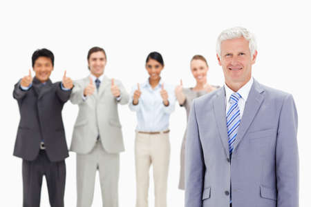 thumbsup: Close-up of a multicultural business team with their thumbs-up with a mature man in foreground LANG_EVOIMAGES