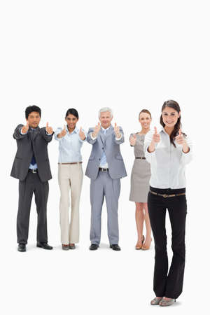 thumbsup: Smiling business team with their thumbs-up with a woman in foreground against white background