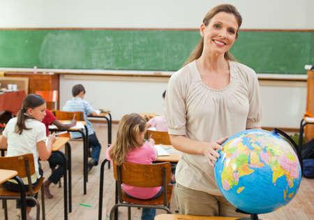 holding globe: Smiling elementary teacher holding globe