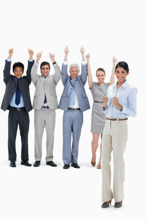 thumbsup: Multicultural business team raising their arms and giving the thumbs-up with a woman clenching her fists in foreground against white background LANG_EVOIMAGES