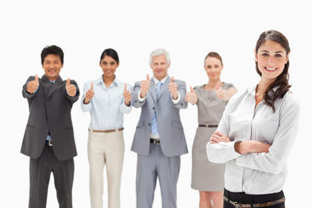 thumbsup: Close-up of a smiling multicultural business team with their thumbs-up focus on a woman with her arms folded in foreground LANG_EVOIMAGES
