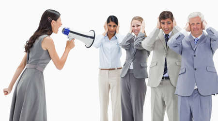 hands over ears: Woman yelling in a megaphone at business people with their hands over their ears against white background