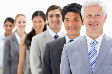 single line: Close-up of smiling business people in a single line with focus on the first person against white background LANG_EVOIMAGES