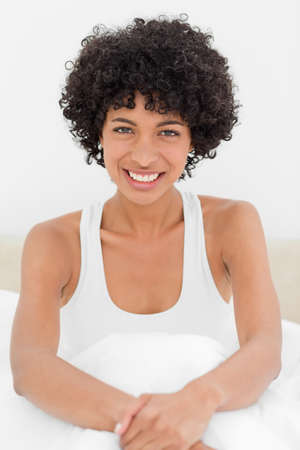 haired: Close-up of a frizzy haired woman smiling in her bed