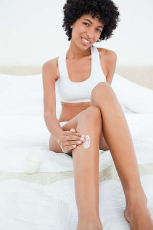 head tilted: Portrait of a beautiful woman applying cream on her leg while sitting on her bed LANG_EVOIMAGES