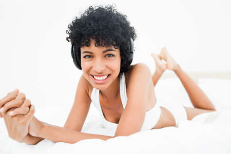 frizzy: Frizzy haired woman lying on the belly in her bed while wearing a headphone