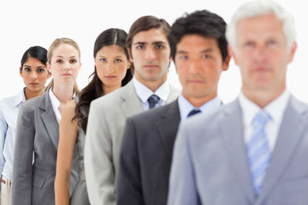 single line: Close-up of business people in a single line with focus on the fifth person against white background