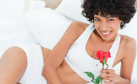 frizzy: Portrait of a seductive frizzy woman on her bed  holding a rose in a bright bedroom LANG_EVOIMAGES