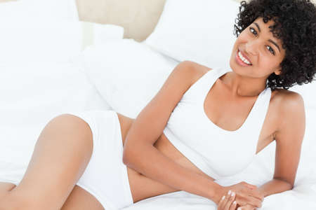 head tilted: Portrait of a smiling sexy woman on her bed in a bright bedroom
