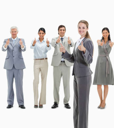 approving: Blonde woman smiling with business people approving behind her against white background