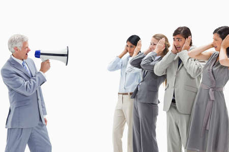 hands over ears: Man yelling in a megaphone at business people with their hands over their ears against white background LANG_EVOIMAGES