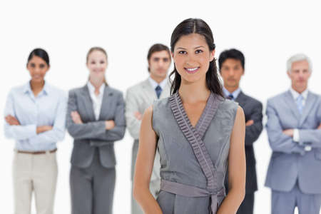 team from behind: Woman with business team behind her against white background LANG_EVOIMAGES