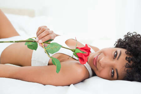 frizzy: Portrait of a frizzy woman lying on her bed with a rose in a bright room