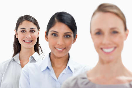 single line: Close-up of smiling businesswomen in a single line with focus on the last person against white background