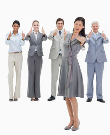 thumbsup: Woman doing a wink with a business team with their thumbs-up against white background